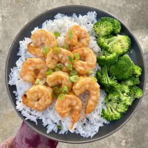 Plate of shrimp and broccoli over rice